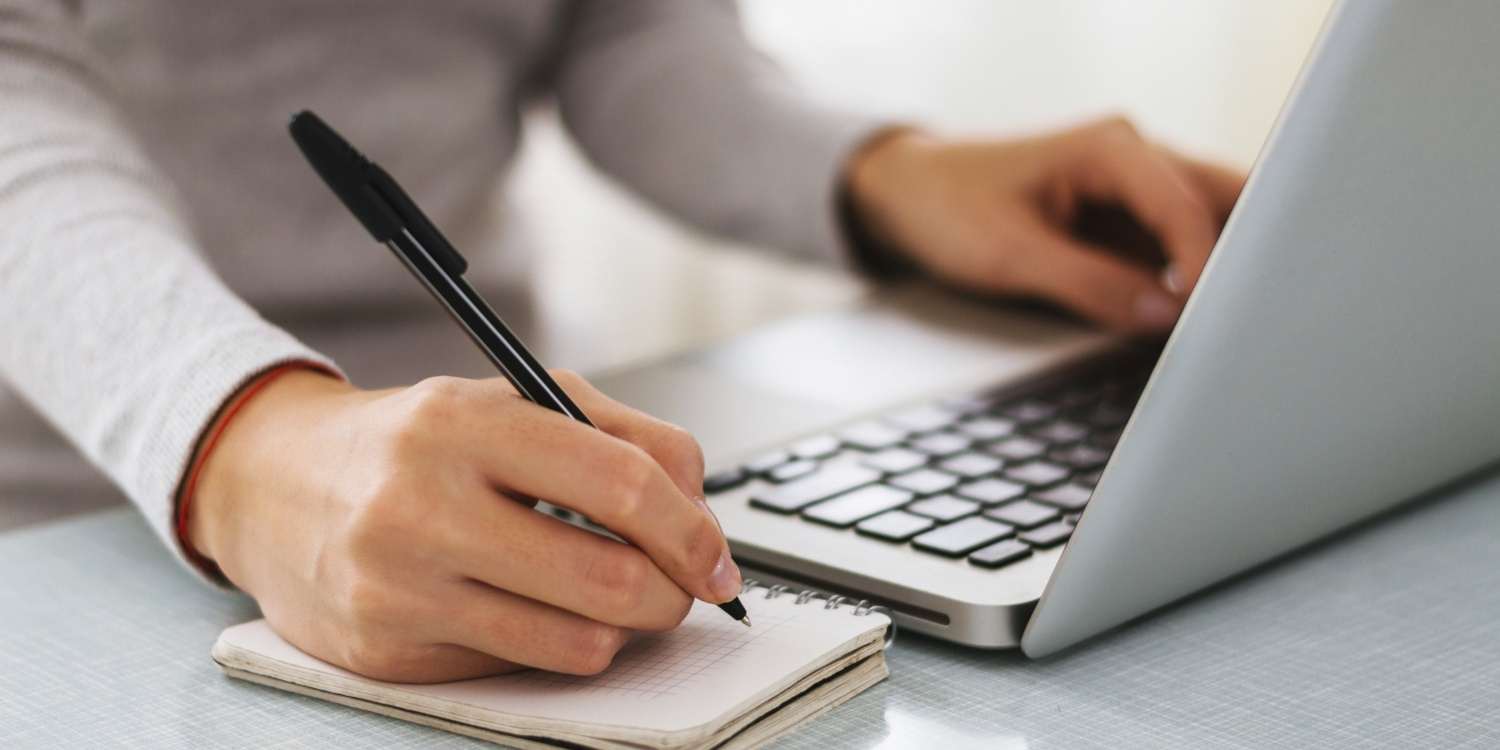 Businesswoman_writing_with_computer_and_notepad-001486-edited