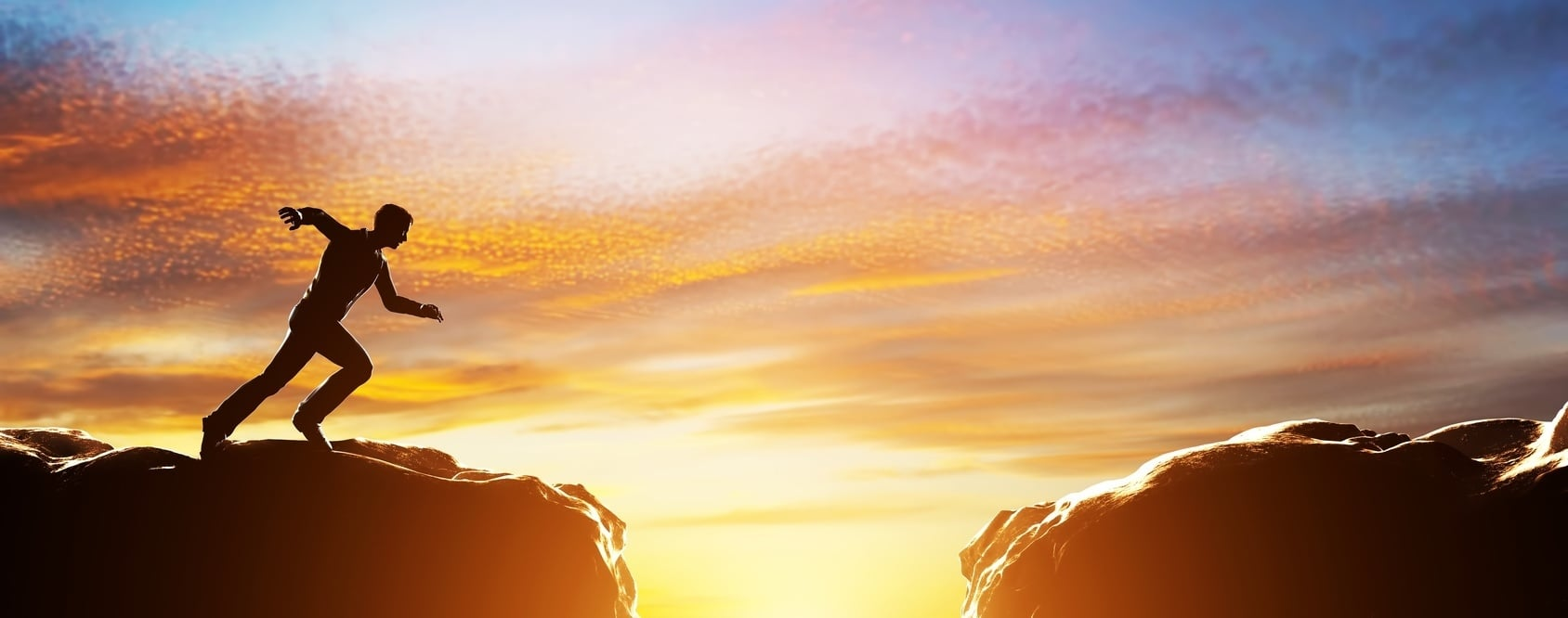 Silhouette_of_person_jumping_chasm_cliff_gap_sunset_action_challenge-006100-edited.jpg